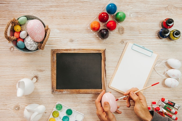 Hand painting egg at table with blackboard