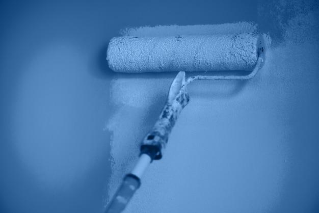 Ручная роспись стены с валиком в монохромном цвете. ремонт квартир, ремонт, строительство и концепция дома. модный синий и спокойный цвет. инструменты для покраски стен.