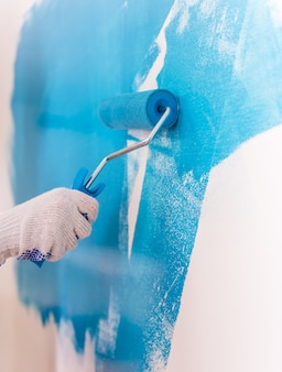 Hand paints a white wall in light blue.