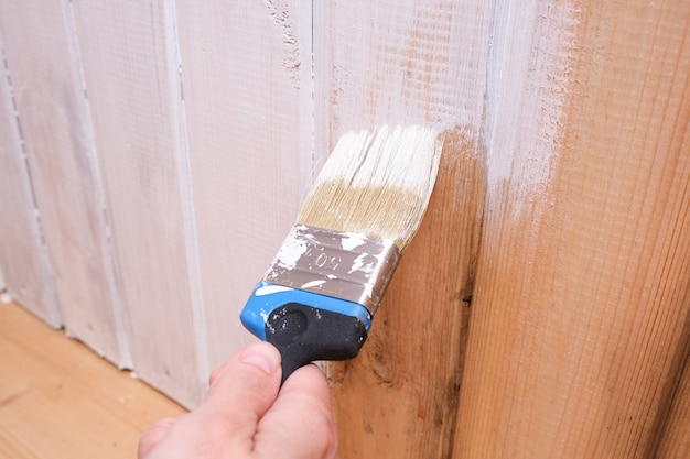 A hand paints a wooden surface wall with white acrylic paint, home repair and restoration.
