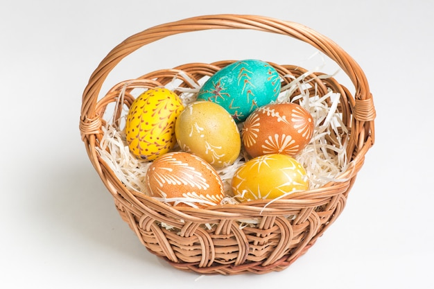 Hand-paited easter eggs in brown basket on white