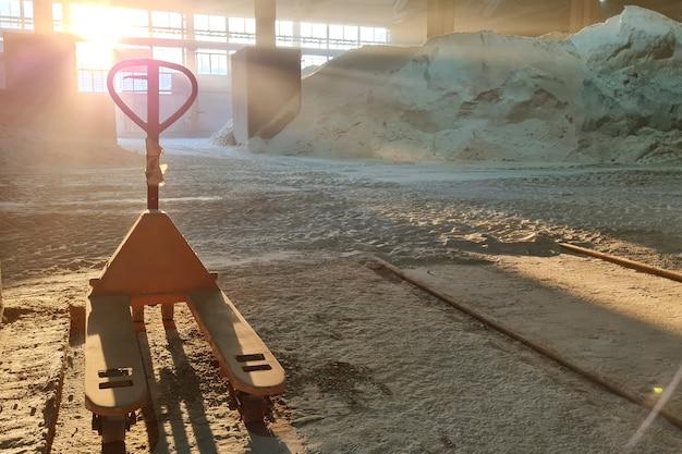 ミネラル肥料倉庫のハンドパレットトラック。人はいません、後ろの太陽の光。