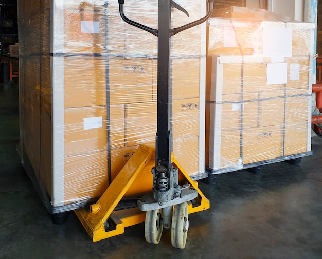 Hand pallet truck with cargo pallet shipment at the warehousing.