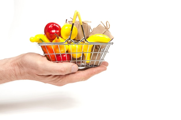 In  hand in the palm of your hand a shopping basket full of fruit and gift boxes with bows on white