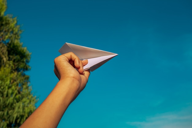 Hand and paper plane in the sky