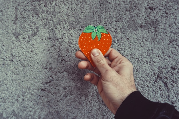 Hand and paper strawberry
