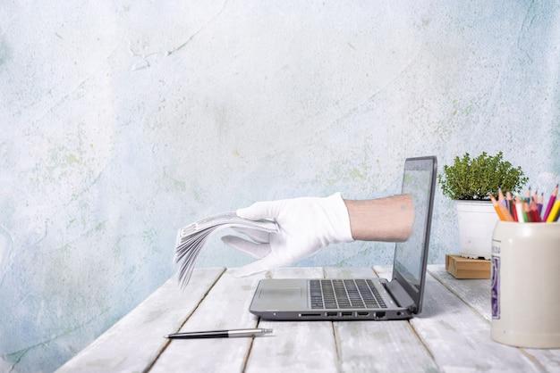 Оплачивайте пачку счетов, выходящих из экрана ноутбука. получите деньги в интернете. онлайн-оплата или сделка. получите деньги онлайн concept.copy space