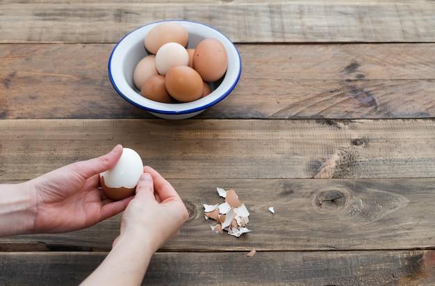 Ручная чистка вареных яиц. деревянная поверхность. скопируйте пространство. чаша с яйцами.