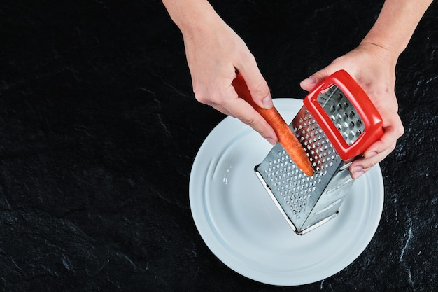 Рука очищает морковь на белой тарелке на черном.