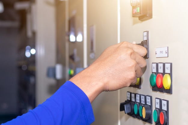 Hand of people key switch select mode in electrical control panel contains
