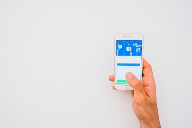 Mano, telefono, app facebook e copia spazio