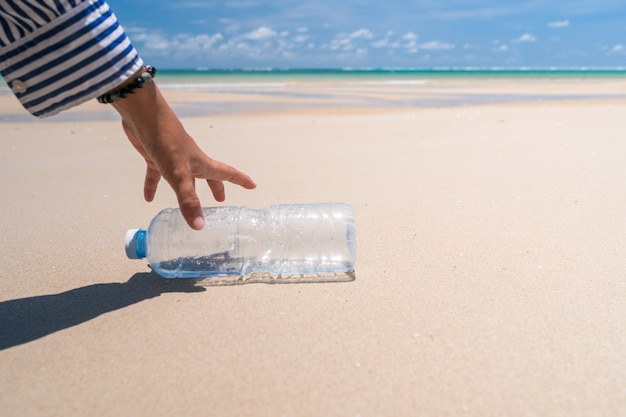 Hand pick up empty water bottle or trash at beautiful beach. environment global warming issue.