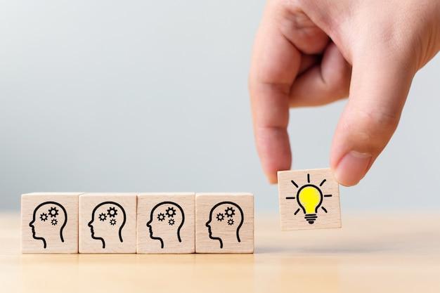 手は、人間の頭のシンボルと電球アイコンの木製キューブブロックを選ぶ