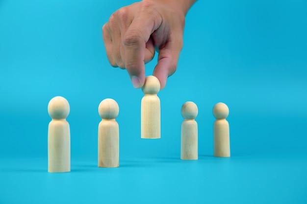 ビジネス組織とリーダーシップのための人の木人形の概念人的資源を手で選びました。