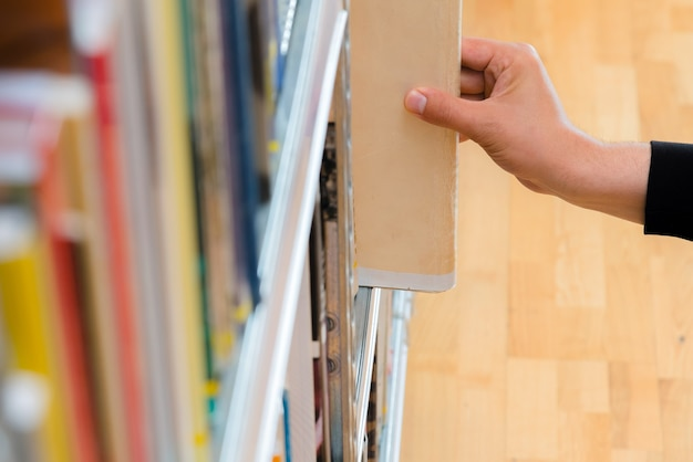 Hand picking a book from the shelf in the library.