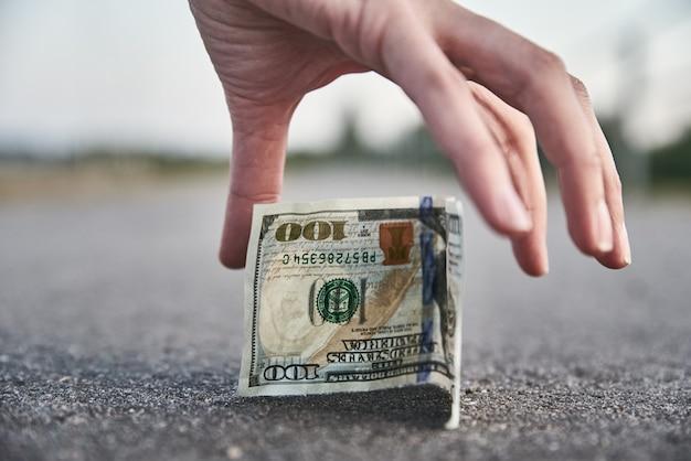 Рука сбор стодолларовой банкноты с земли. нашли денежную концепцию