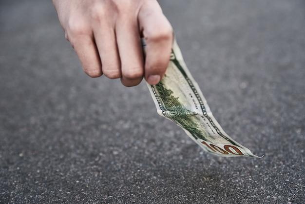 Рука сбор стодолларовой банкноты с земли