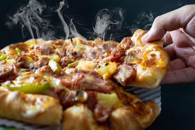 Hand picking sliced pizza with cheese ham bacon and pepperoni on black background