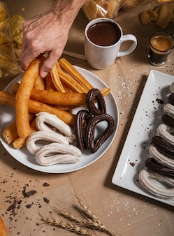 Hand picking up a churro from the table plate with a cup of chocolate. a popular concept of spanish breakfast.