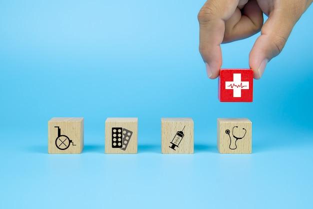 他の医療アイコンとキューブ木製おもちゃブロックのヘルスアイコンを拾う手。