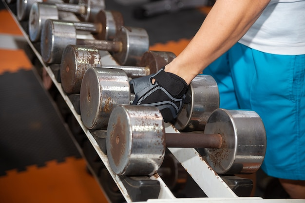 Hand picking up old dumbbell on the rack