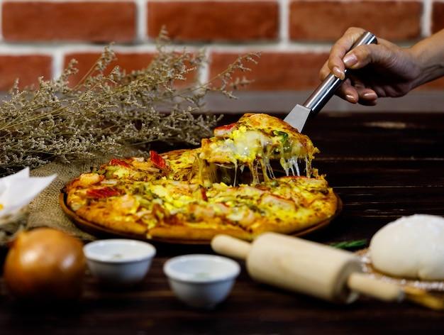 노란색의 뜨거운 맛있는 해산물 피자를 손으로 집어 들고 장식된 말린 꽃과 요리 도구로 가득한 테이블에서 고전적인 식사를 위한 고급 전통 이탈리아 음식으로 제공되었습니다.
