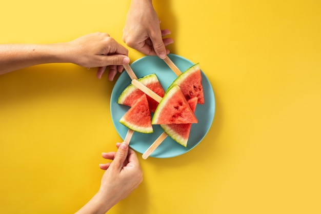 Hand picking up watermelon slices popsicles on blue plate and yellow.