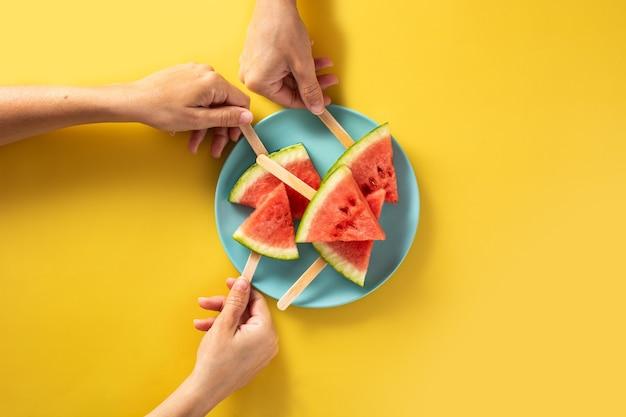 Рука собирает фруктовое мороженое ломтиками арбуза на синей тарелке и желтом.
