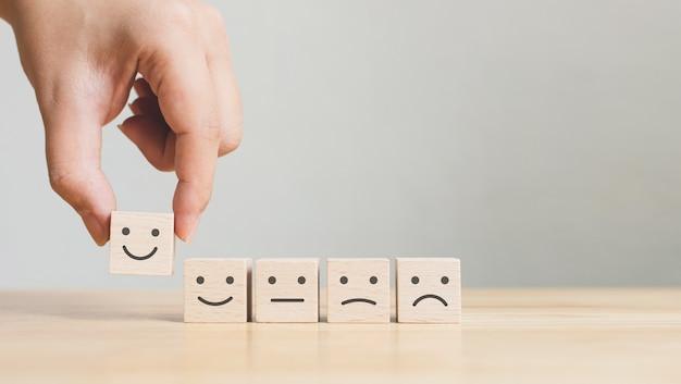 Рука поднимает деревянные кубики с грустными лицами на них