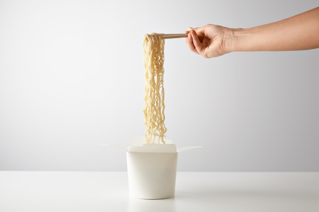 Hand picks up tasty boiled noodles from opened wok takeaway blank paper box isolated on white in center