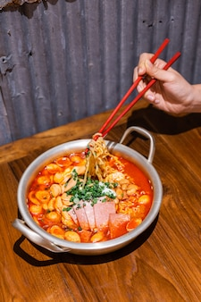 箸で麺をつまんで手。キムチ、ハム、ソーセージ、木製のテーブルにシルバーボウルにチーズの伝統的な韓国のラーメンスープ。韓国料理。おいしいアジア料理。