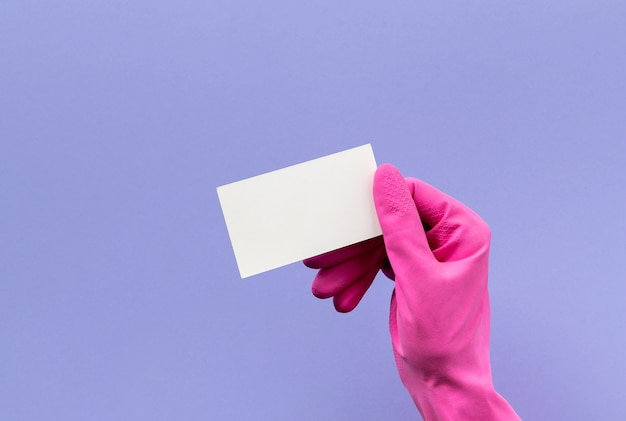 Hand in pink rubber glove holding business card on purple background. cleaning service or housekeeping mock up.