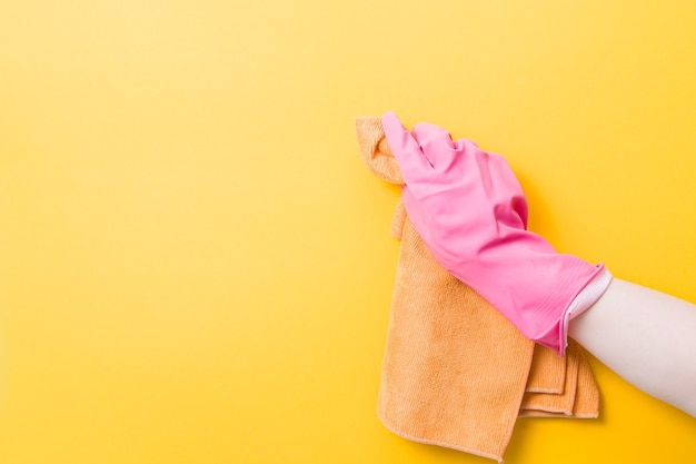 Hand in a pink rubber glove holds an orange rag for washing and cleaning