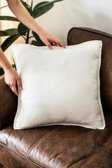 Рука кладет белую подушку на кожаный диван