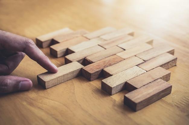 ゲームを成功させ、戦略を成功させるために木ブロックを配置し引っ張る手