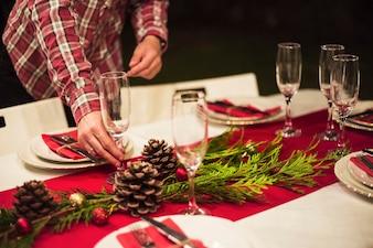 Hand placing champagne glass on Christmas table
