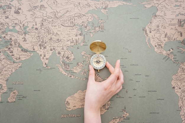 Hand placing a compass on a world map