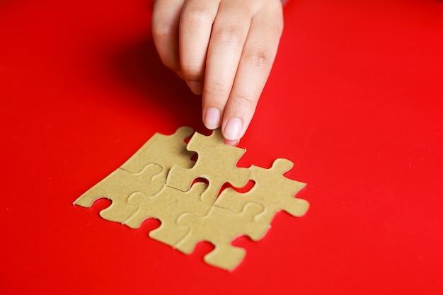 Рука помещает последний кусок головоломки на красном фоне