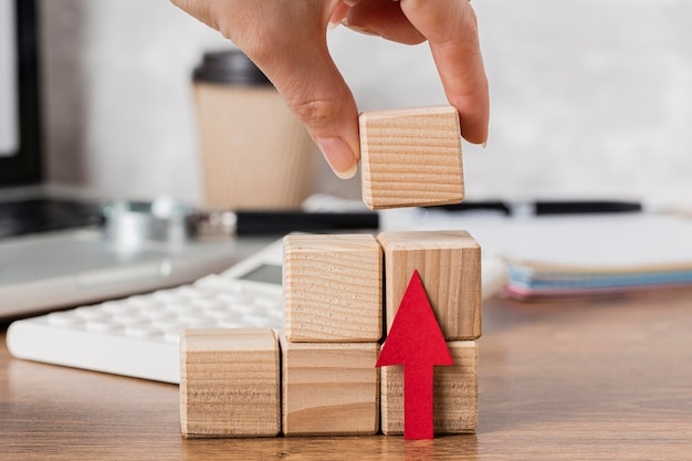 Рука помещает деревянный блок, чтобы обозначить рост