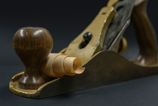 Hand plane on a black background. shavings