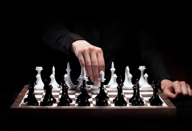 Hand playing chess in darkness