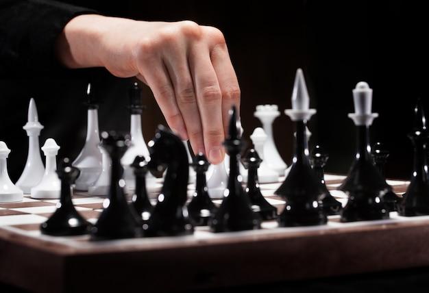Рука играет в шахматы в темноте