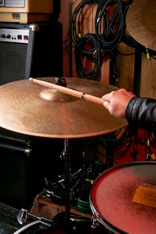 Hand playing on cymbal with stick