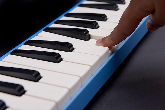 黒の背景を持つピアニカブローオルガン楽器を演奏する手