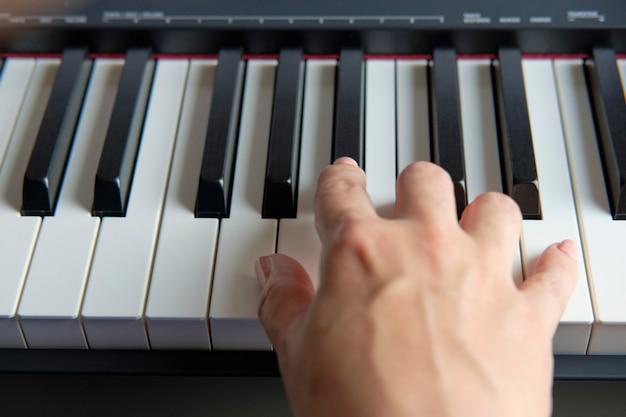 손 연주 피아노, 포르토피아노, 신디사이저. 부분적으로 표시된 피아노 건반 클로즈업
