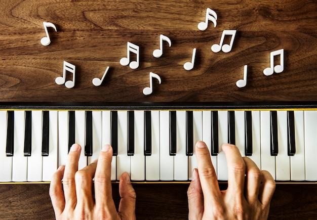 Рука играет на пианино на деревянном столе