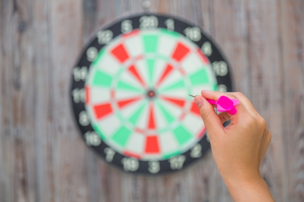 Hand pointing a dart to a target