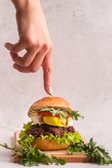 Hand pointing to a delicious hamburger