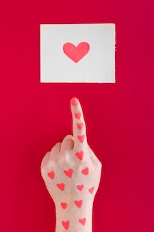 Hand pointing finger at heart drawing