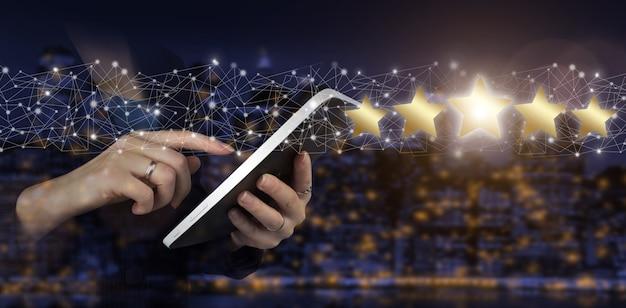 회사의 등급을 높이기 위해 5개의 별 기호를 가리키는 손. 디지털 홀로그램 5개의 별이 있는 손으로 터치하는 흰색 태블릿은 도시의 어두운 흐릿한 배경에 표시됩니다. 제품 서비스 평가 개념입니다.
